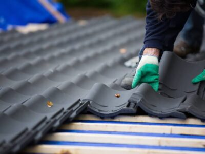 This is an image of a roofing contractor replacing damaged roof tiles.