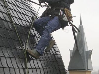 This is an image of a professional roofing contractor doing roof inspection and maintenance on a tower.